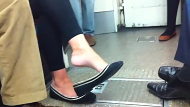 Candid blonde milf dangling her flats in train